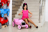 Beautiful girl sitting on the stairs next to the toy car — Stock Photo