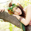 Young beautiful girl lying on a tree trunk — Stock Photo