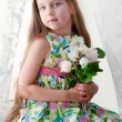 Adorable little girl sitting by the window with the flowers — Stock Photo