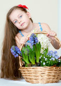 Pretty little girl with spring flowers in basket — Stock Photo