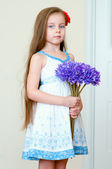 Adorable little girl with the flowers — Stock Photo