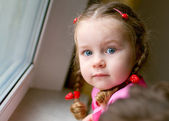 Adorable little girl with braids by the window — Stock Photo