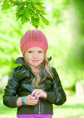 Adorable little girl in pink hat smiling in a park — Stock Photo