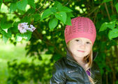 Adorable little girl in pink hat smiling in a park close-up — Stock Photo