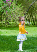 Adorable little girl blowing soap bubbles — Stock Photo