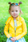 Pretty little girl smiling in a park — Stock Photo