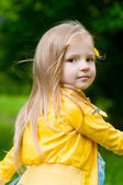 Adorable little girl with long hair in yellow jacket — Stock Photo