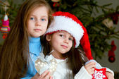 Two adorable girls in front of christmas tree — Stock Photo