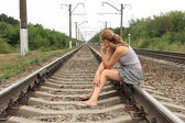Pensive, sad girl sitting on the rails of the railway — Stock Photo