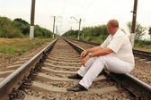 Thoughtful man sitting on railroad tracks — Stock Photo
