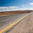 Desert road with blue car - Stock Photo