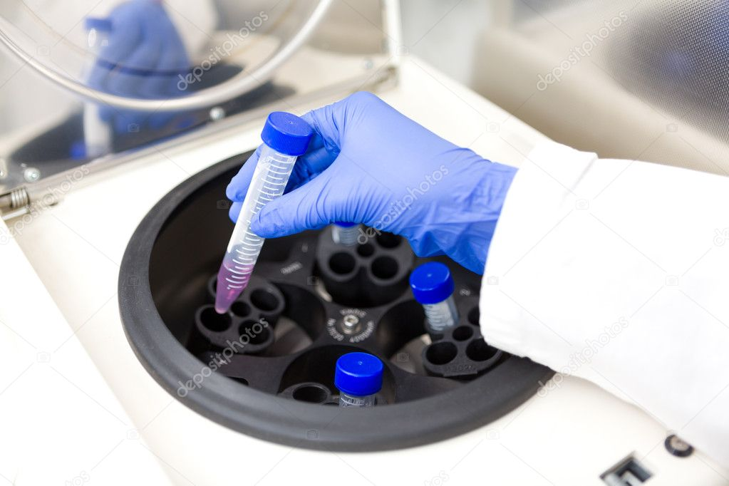 Scientist putting test tube into centrifuge — Stock Photo #10948066