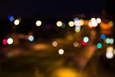 Blurred road with city lights at night — Stock Photo