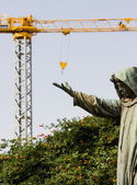 Funny image of a statue catching crane hook — Stock Photo