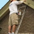 Painter painting exterior trim - Stock Photo