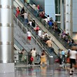 Blurred crowd moving up an escalator - Stock Photo