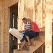 Young couple looking at the blue prints of their new home — Stock Photo