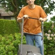 Man cutting the lawn - Stock Photo