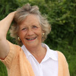 Stock Photo: Smiling lady in her sixties, outside in garden