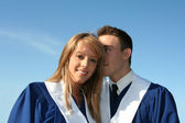 Cute couple in graduation gowns — Stock Photo