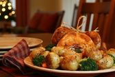 Roast turkey, potatoes, onions, broccoli and carrots, Christmas tree in background — Stock Photo