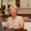 Grand-min kitchen using her laptop — Stockfoto #11361785