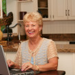 Grand-min kitchen using her laptop — Stock Photo #11361785