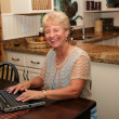 Grand-ma in the kitchen using her laptop — Stock Photo