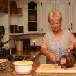 Grand-ma in a country kitchen carving a beef roast — Stock Photo