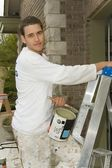 Young man, holding a can of paint and ladder — Stock Photo