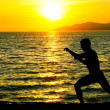 Silhouette of man practicing karate on a sunset beach. — Stock Photo