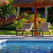Pool side lounge chairs at a tropical resort. - Stock Photo