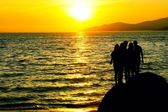 Silhouette of five teens standing on a rocky beach at sunset. — Stock Photo