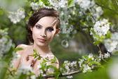 Beaty girl in blooming garden — Stock Photo