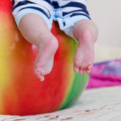 Baby feet on the ball — Stock Photo