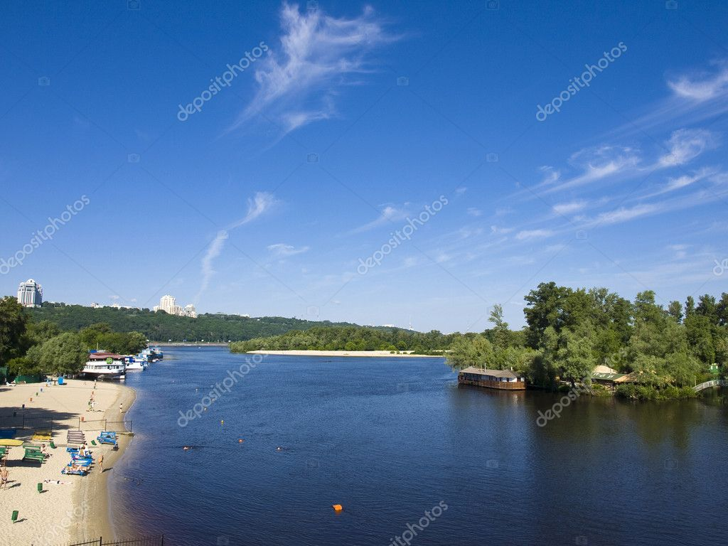 Sandy beach on the river bank. Near the beach moored by boats and floating restaurant. Everything is very green. Among the greenery of several high-rise buildings. A lot of sky and water. — Stock Photo #11084810