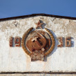 Stock Photo: Coat of arms of USSR on facade of old barracks