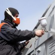 Stock Photo: Commercial painter on stairs spray painting steel exteri