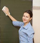 Schoolgirl washes chalkboard — Stockfoto