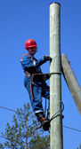 Electrician on a pole makes installation work — Stock Photo