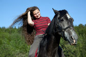 A girl with flowing hair on a black horse — Foto Stock