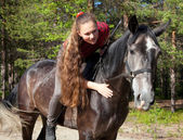 A girl with her hair stroking horse — Stock Photo