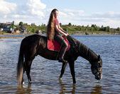 La jeune fille conduire un cheval à l'eau — Photo