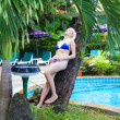 Stock Photo: Blonde by pool among palm trees