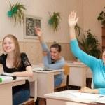 Schoolgirl in class raised their hands — Stock Photo