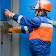 Caucasian electrician working on a panel - Stock Photo