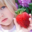 Girl with big strawberry — Stock Photo