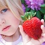 Girl with big strawberry — Stock Photo