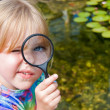 Stock Photo: Girl with magnifying glass