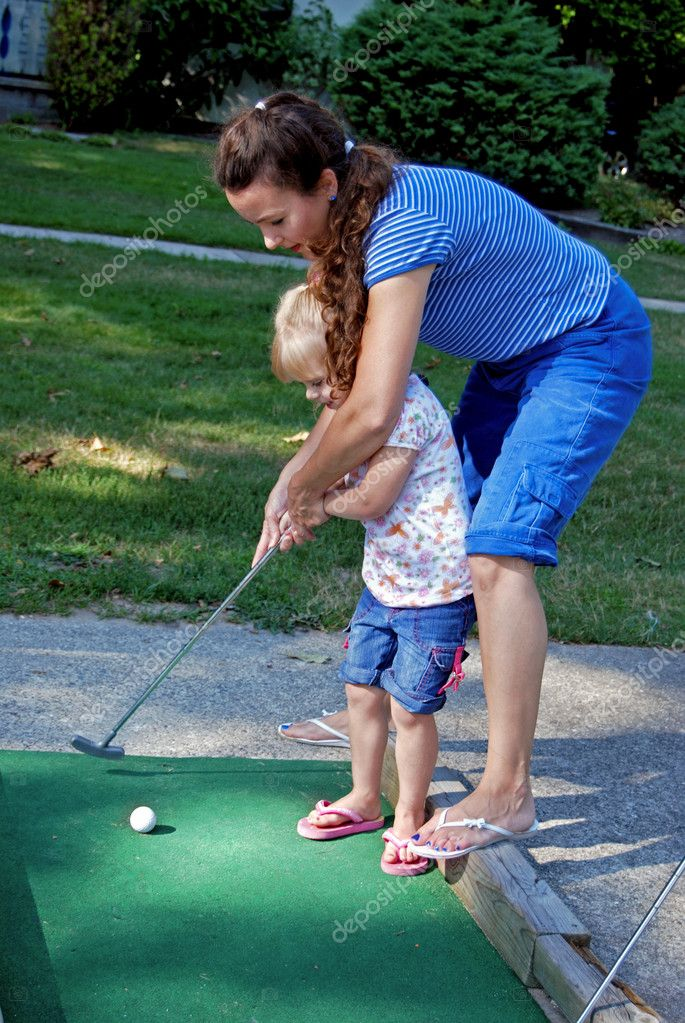 Mother teaching her daughter to golf.   #11051449